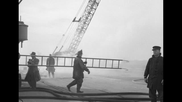 vídeos y material grabado en eventos de stock de rear shot firemen survey damage on dock, with smoke wafting, fire hoses stretching across the dock, ship in background, debris at right, and signal... - poste de madera