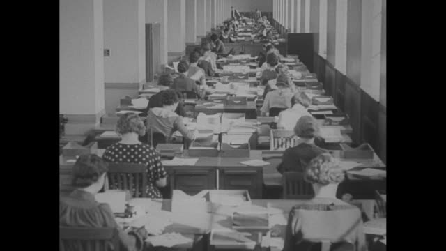 ls rear shot int department of justice office area with pairs of women seated at long tables working / male investigator examines a fingerprint card... - filing cabinet stock videos & royalty-free footage