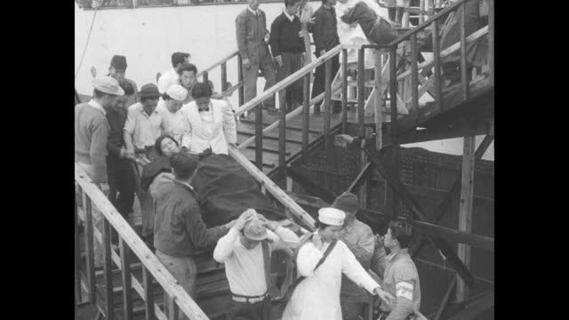 rear shot japanese men in maizuru harbor building watch as helicopter passes by during arrival of repatriated japanese people from china / nurses and... - emigration and immigration点の映像素材/bロール