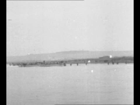 stockvideo's en b-roll-footage met rear shot landing barge heads for coast of north africa during world war ii / ws african shoreline with mountains in background men wading toward... - generaal militaire rang