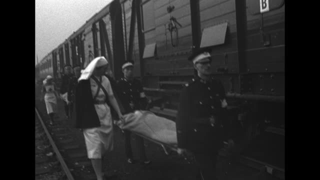 Rear shot nurses and medics carry wounded Londoners to hospital train during World War II / CU female patient on stretcher / montage medics carry...
