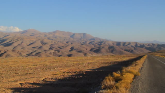 Rear shot of driving on a road in the desolate Atacama desert mountains