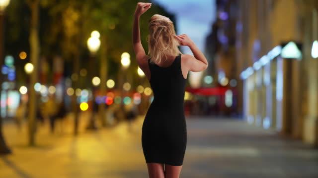 rear shot of sensually dancing blonde caucasian female outside on sidewalk - black dress stock videos & royalty-free footage