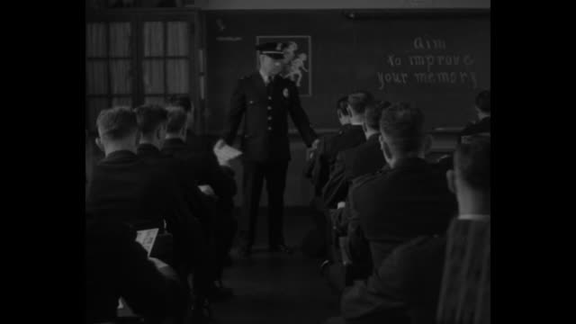"""rear shot patrolmen in training class in classroom, facing officer and blackboard at front of room / officer points at phrase on blackboard """"aim to... - mug shot stock videos & royalty-free footage"""