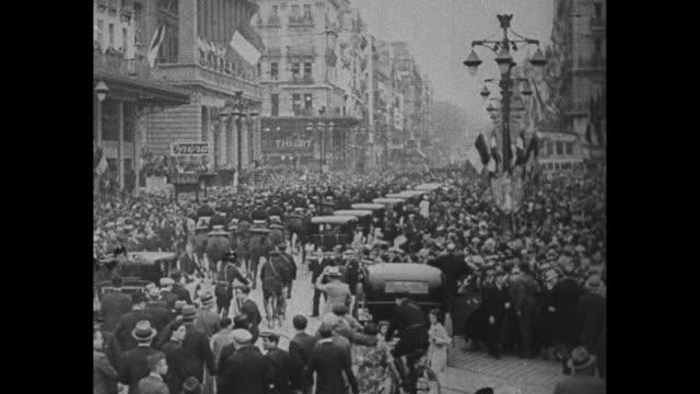 vídeos de stock e filmes b-roll de rear shot procession marches on marseille street / king alexander i of yugoslavia smiles from open area of car while seated next to french foreign... - grade de radiador