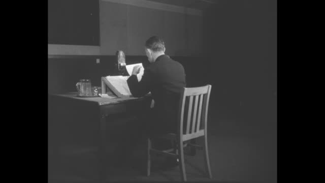 Rear shot radio announcer sits down at table in studio with engineer in background / indicator light blinks on wall / montage announcer speaks VO...