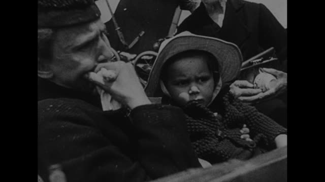 rear shot soldiers in fg look on as line of refugees moves in city street / ext building douane belge / soldiers watch as bicycling refugees pass /... - little girls giving head stock videos and b-roll footage