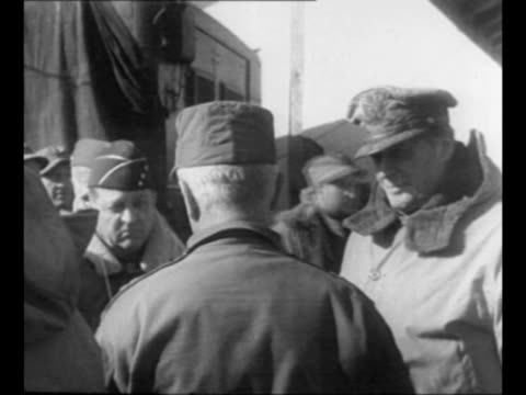 Rear shot Supreme Commander of the United Nation Command forces in Korea Douglas MacArthur listens as field commander speaks / MacArthur and Lt Gen...