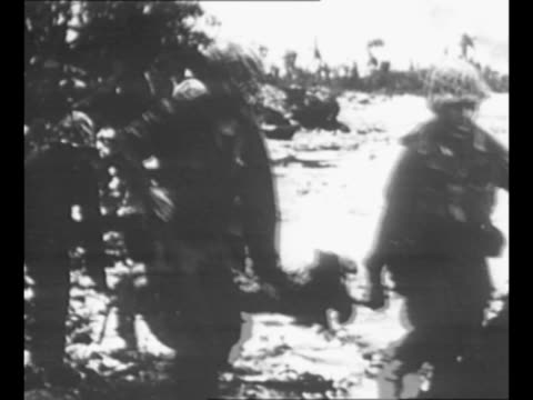 rear shot us marines advance to airfield on peleliu island during world war ii as plane flies above / marine runs in jungle area / marines with tank... - carrying pole stock videos & royalty-free footage