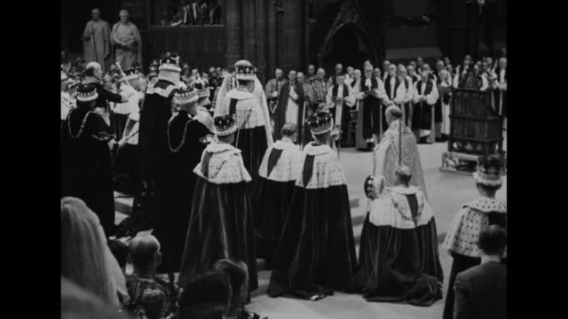 Rear side view newly crowned Queen Elizabeth II on dais surrounded by Archbishop of Canterbury and peers wearing elaborate robes and coronation...