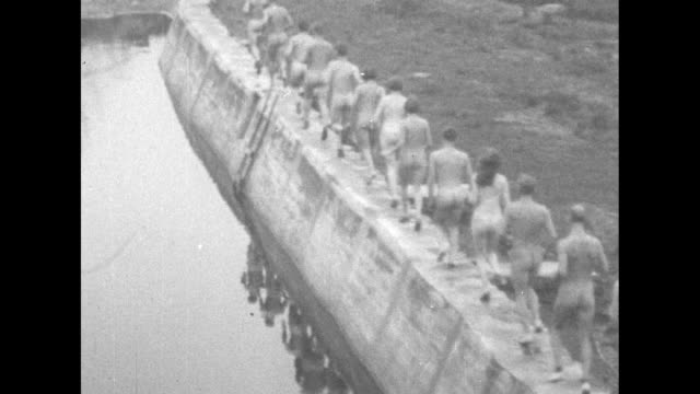 rear slo-mo shot naked men and women run atop a stone dam / vs normal speed rear shots of the nudists running along the stone dam / note: exact year... - fkk stock-videos und b-roll-filmmaterial