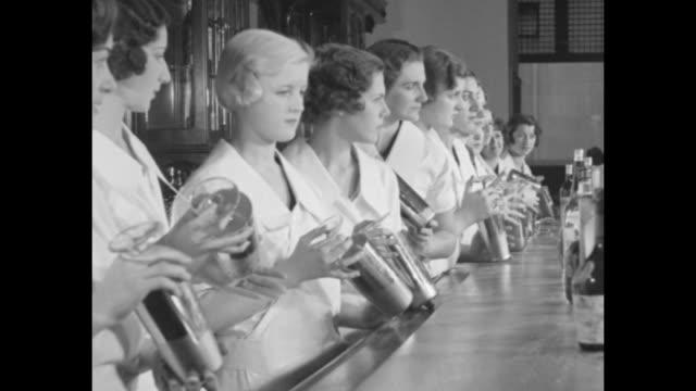 vidéos et rushes de rear tilt-down shot line of young women, all dressed in white, stands at bar in tavern as bartender/instructor faces them; bottles of liquor line... - shaker