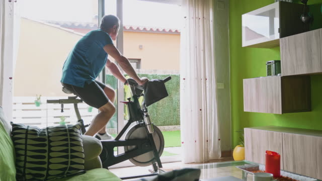 rear video view of mature man working out on exercise bike at home - cardiovascular exercise stock videos & royalty-free footage