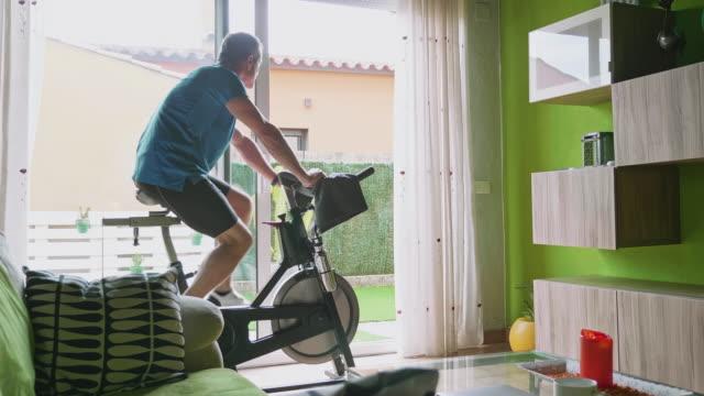 vídeos de stock, filmes e b-roll de vista de vídeo traseira de homem maduro malhando em bicicleta de exercício em casa - rotina