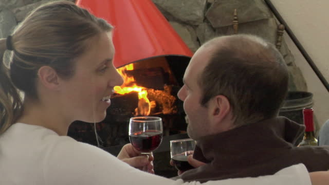 cu, rear vie of couple kissing and drinking wine in front of fireplace in mountain cabin, whitefish, montana, usa - in front of stock videos & royalty-free footage