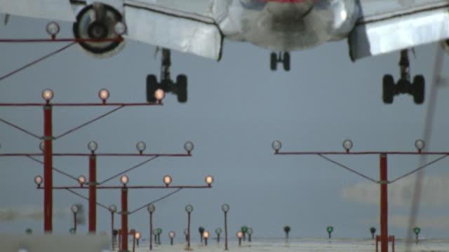 rear view airplane landing on runway with lights in foreground / los angeles, california - landefahrwerk stock-videos und b-roll-filmmaterial