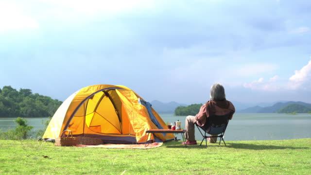 背面図:単独のシニア男性は、湖に沿ってコーヒーやキャンプでリラックスして週末の時間を過ごす - キャンプする点の映像素材/bロール