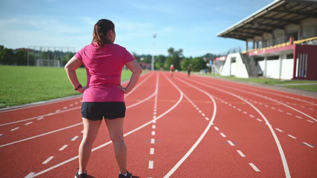 rear view asian chinese body positive woman standing facing running track with arms akimbo - hand on hip stock videos & royalty-free footage