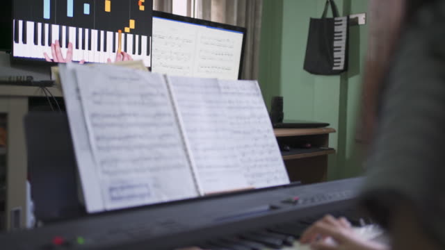 rear view asian girl learning to play basic piano by using electric synthesizer keyboard from internet self studying at home - one teenage girl only stock videos & royalty-free footage