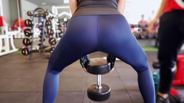 vidéos et rushes de vue arrière - femme asiatique faisant le squat utilisant l'haltère à la gymnastique - fesses