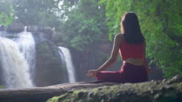 Rear view Asian woman practicing or doing yoga at the waterfall, Lotus pose on meditation session. Beautiful Landscape, Natural background, Thailand.