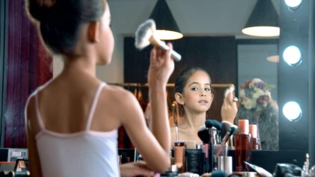 vídeos de stock, filmes e b-roll de vista traseira: menina da bailarina que pinta sua face que olha o espelho - pintor artista