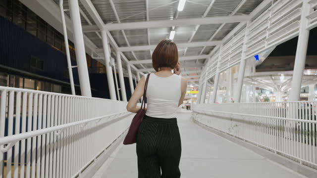 vídeos de stock e filmes b-roll de rear view beautiful asian woman wearing a protective face mask walking and using smartphone, new normal concept, people lifestyle after covid-19 - cabelo curto comprimento de cabelo