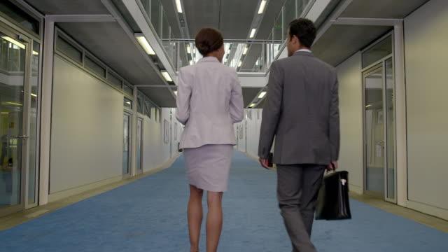 vídeos de stock, filmes e b-roll de ws rear view businessman and woman walking along galleried corridor - vista traseira