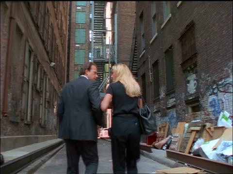 stockvideo's en b-roll-footage met rear view businessman + blonde woman walking in alley arguing / nyc - minder dan 10 seconden
