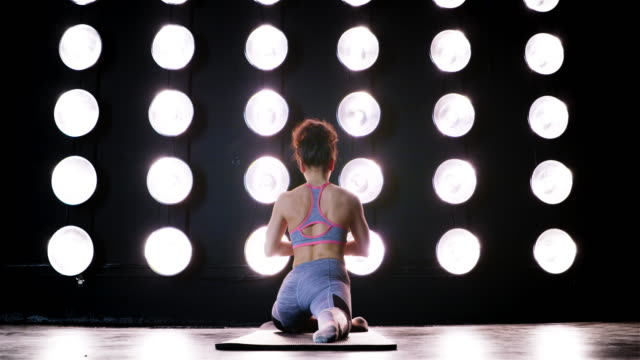 rear view fit young woman doing stretches on floor mat during workout 4k - vesper stock stock videos & royalty-free footage