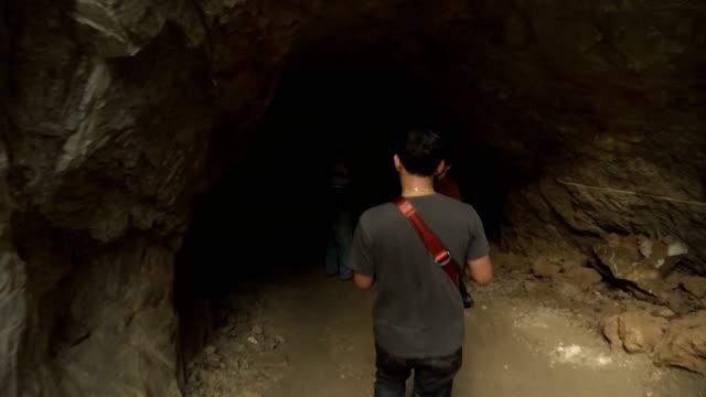 vídeos de stock, filmes e b-roll de vista traseira: seguindo a família viajante entrar em caverna na floresta antiga, uthaithani, tailândia - pouca luz