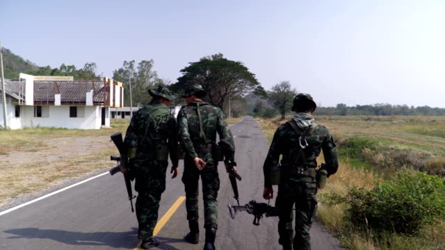 rear view: following group of fully Equipped and Armed Soldier walking on the road