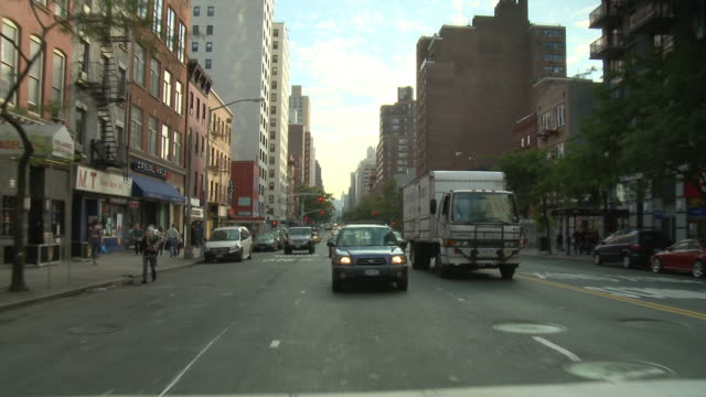 POV Rear view from car driving down 3rd Avenue in the Bowery and East Village / New York City, New York, United States