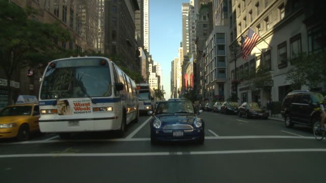 pov rear view from car driving down street with bus and mini cooper / new york city, new york, united states - new stock videos and b-roll footage