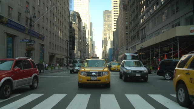 pov rear view from car driving down street with taxis and a lincoln town car / new york city, new york, united states - lincoln town car stock videos and b-roll footage