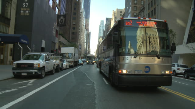 POV Rear view from car driving in down street with buses / New York City, New York, United States