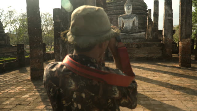 rear view from close-up to wide view: Thai traveler is taking the photo in temple at Sukhothai, Thailand