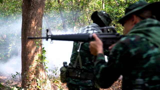 rear view: group of fully Equipped and Armed Soldier disappear among mist in tropical forest