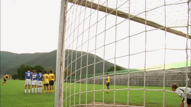 rear view long shot players lined up for free kick / goalkeeper blocking shot - 20 29 years stock videos & royalty-free footage