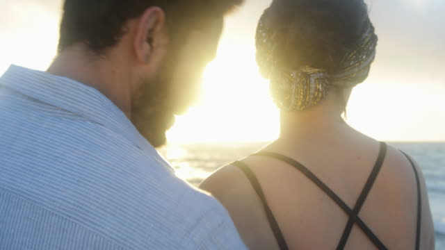 cu rear view man and woman being tender with each other while watching sunrise - tulum mexico stock videos & royalty-free footage