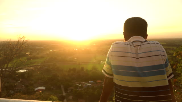 rear view: man on top of mountain in rural town under sunset - twilight stock videos & royalty-free footage