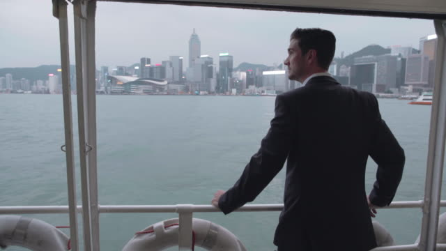 ws rear view man standing on star ferry, hong ong - star ferry stock videos & royalty-free footage
