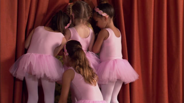 rear view medium shot girls wearing tutus peeking through curtain on stage - nosy stock videos and b-roll footage