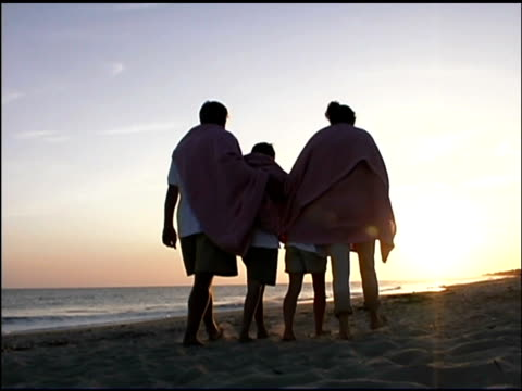 rear view medium shot of a family walking arm in arm together on the beach at sunset. they have a blanket wrapped around them. - see other clips from this shoot 1135 stock videos & royalty-free footage
