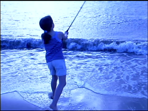 rear view medium shot of a girl standing in the ocean surf at sunset. she turns her body and casts a fishing pole. - see other clips from this shoot 1135 stock videos & royalty-free footage