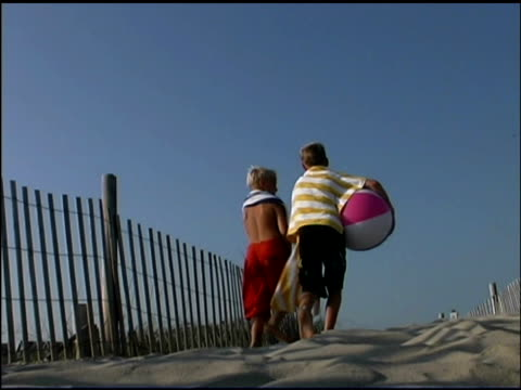 rear view medium shot of two boys walking to the beach. they are wearing swimsuits, holding towels, and carrying beach balls. - see other clips from this shoot 1135 stock videos & royalty-free footage