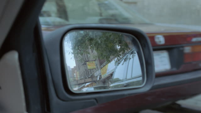 a rear view mirror reflects traffic and storefronts in new york's inner city. - ostamerika stock-videos und b-roll-filmmaterial