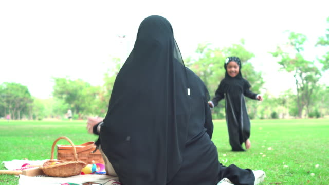 rear view: muslim asian teenage girl wearing a religious dress with feeling love and happiness, running and hugging mother sitting on the carpet at public park for weekend activities. the concept of religious people having a picnic with positive emotion. - religious dress stock videos & royalty-free footage