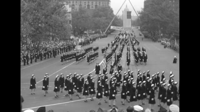 vidéos et rushes de rear view naval officers wave from rear of open top car to crowds gathered along sides of street, us flags hang from lamp post in foreground /... - aircraft point of view