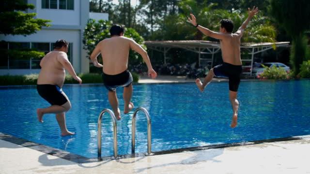 vídeos y material grabado en eventos de stock de slo mo - vista posterior de 3 amigos de salto en piscina - bañador de natación